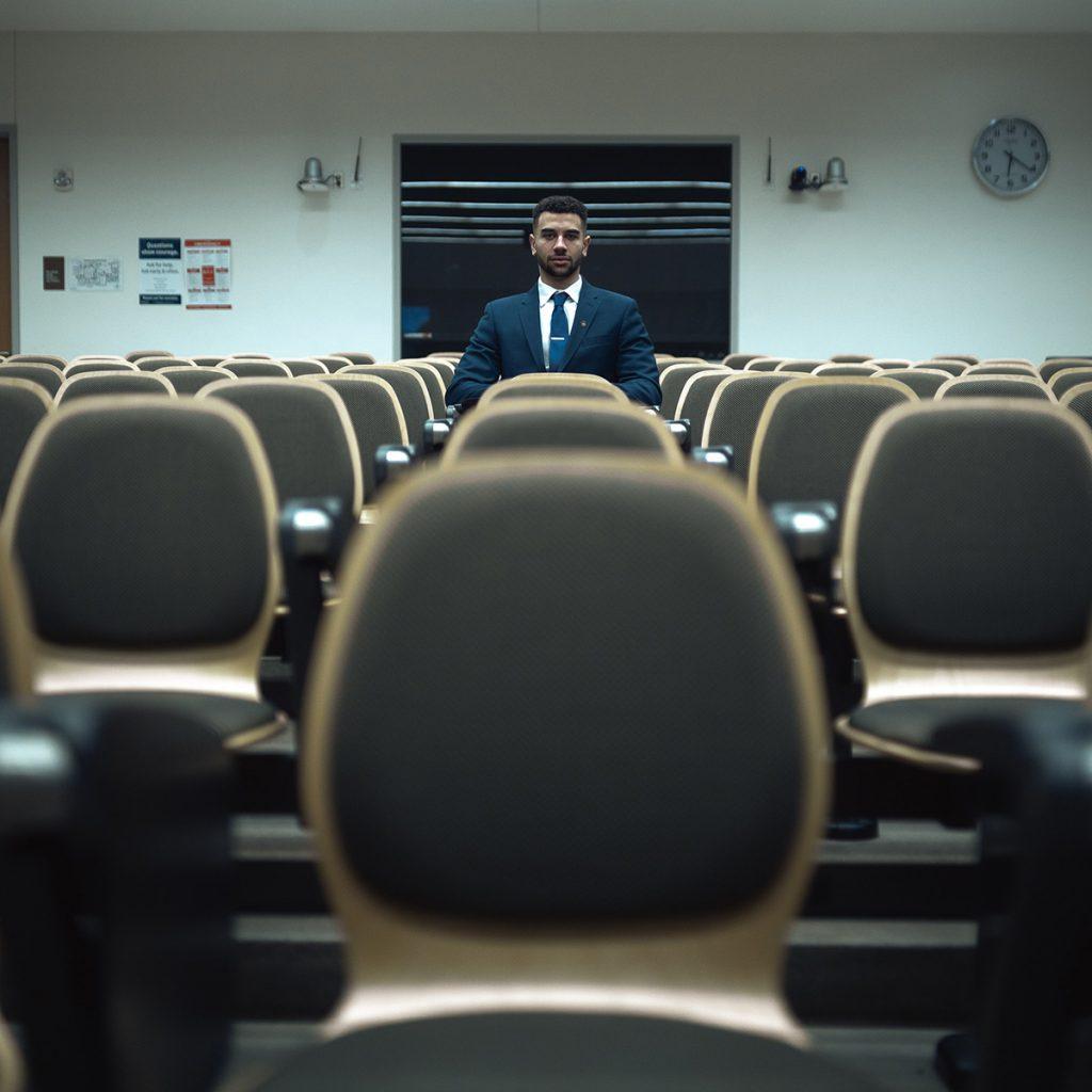 man sitting alone in a seminar room
